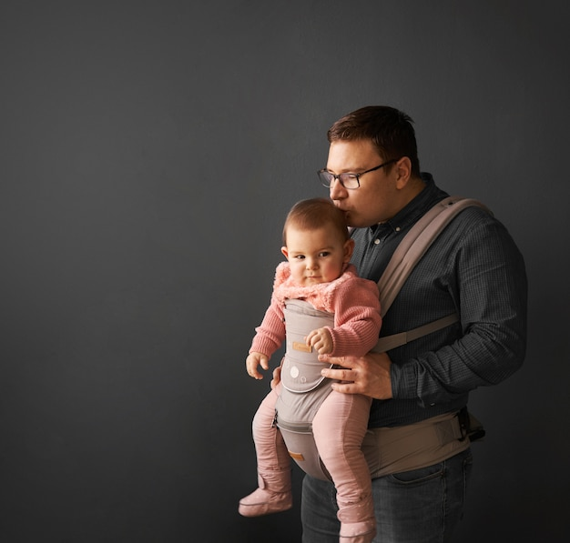 Fathre and his kid in baby carrier at the grey background wall, baby wearing in parenthood
