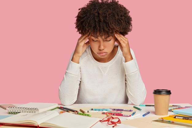 Fatigue african american woman keeps hands on temples, suffers from migraine, sighs with tiredness, works for long time, poses at desk with spiral notepad, takeaway coffee, isolated on pink wall