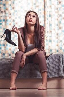 Усталость и стресс после работы. кавказская женщина, брюнетка в костюме, с усталым лицом, сидит на кровати босиком и держит в руках туфли. окно в фоновом режиме.