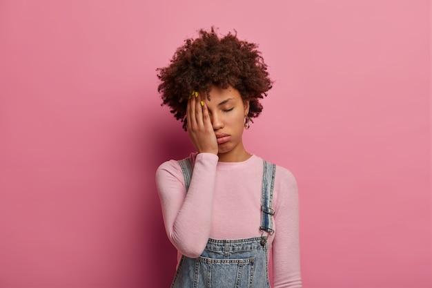 피로한 곱슬 머리의 여성은 지루하고 괴로워하고 자고 싶어하며 손바닥으로 얼굴의 절반을 가리고 눈을 감고 세련된 옷을 입고 분홍색 벽에 포즈를 취합니다. 피로 개념