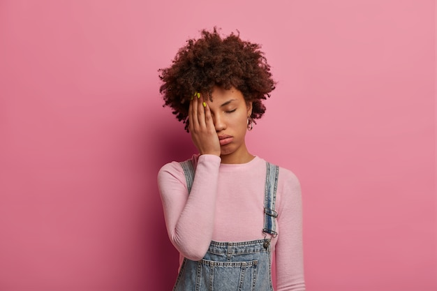 Fatigue curly haired woman feels bored and distressed, wants to sleep, covers half of face with palm, keeps eyes shut, wears fashionable clothes, poses against pink wall. tiredness concept