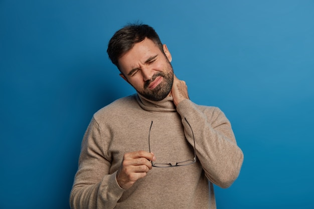 L'uomo barbuto dispiaciuto per la fatica avverte fastidio al collo, ha problemi con la colonna vertebrale