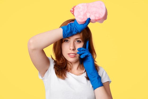 疲労の女性家政婦が疲れから額をこすり、家を掃除し、スポンジを押し、携帯電話で友人に何かを伝え、カジュアルな服を着て、黄色のスタジオの壁に分離