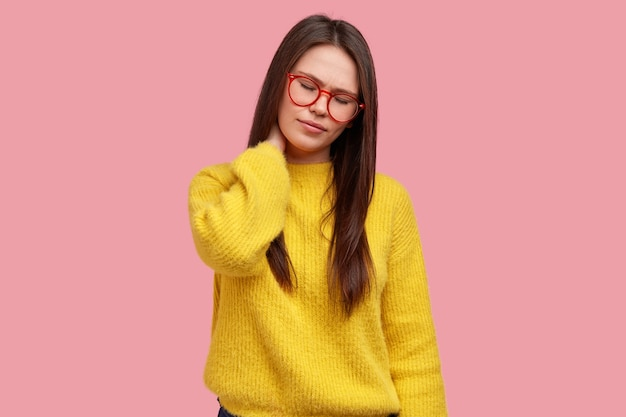 피로 혼혈 젊은 여성이 목을 만지고 통증을 느끼며 앉아있는 생활 방식을 이끌고 눈을 감고 광학 안경과 대형 스웨터를 착용합니다.