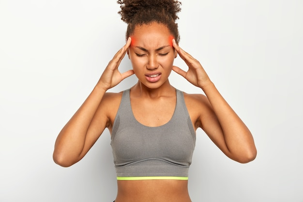 Fatigue overworked afro american woman massages temples, feels strong headache, closes eyes with pain, suffers from migraine, dressed in sport bra, clenches teeth, isolated on white wall