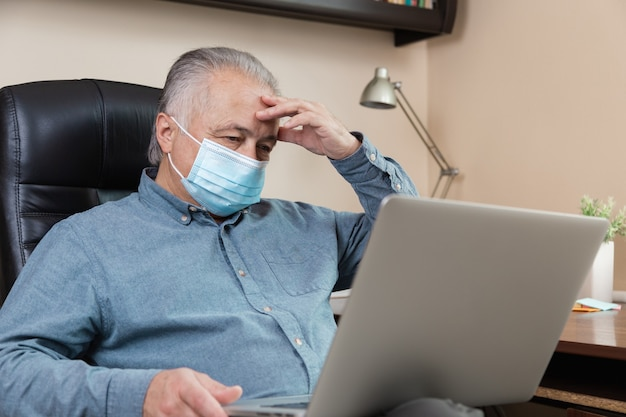 Fatigue senior man in face mask working or communicate on laptop at home. study, training, work, communication, entertainment, leisure during the coronavirus period.