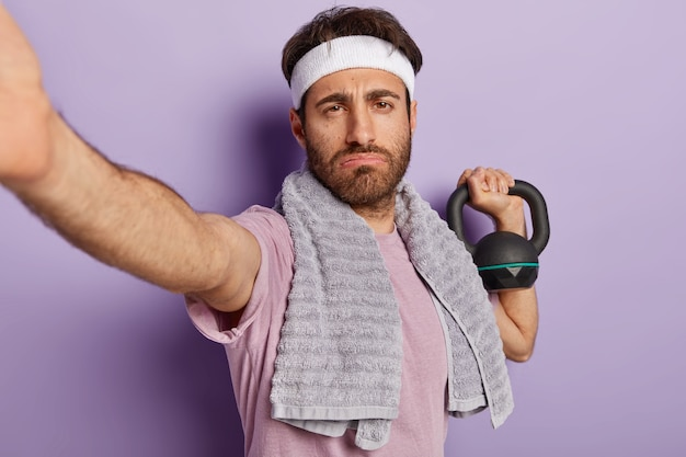 Fatigue serious strong man bodybuilder has exercises with weight, wants to have perfect biceps, demonstrates power and energy, makes selfie, dressed in sportswear, trains in gym. weight lifting