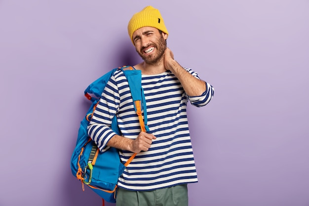 Fatigue tourist touches neck, feels stiffness, dressed in casual clothes, carries rucksack, has painful feelings, looks unhappily at camera, poses over purple background. people and tiredsome journey