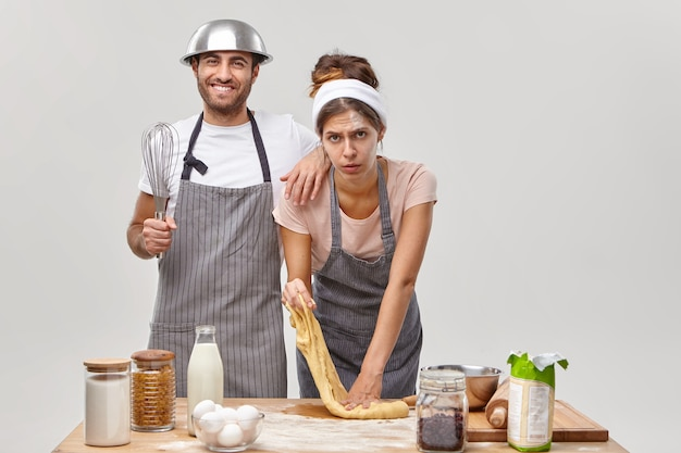 Усталость женщина месит сырое тесто, лепит хлеб, занимается выпечкой, рядом стоит веселый мужчина, одетый в фартук, держит венчик, пытается помочь. два повара выпекают дома кондитерские изделия, пробуют новый рецепт.