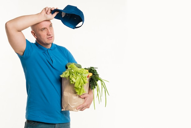 Fatigued delivery man posing with grocery bag