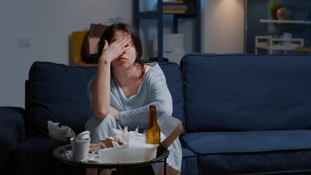 目の疲れや頭痛を和らげようとしている額の橋をマッサージしている疲れた動揺した若い女性...