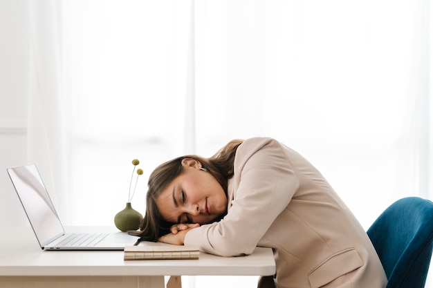 Fatigued woman napping over her laptop