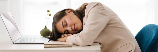 노트북 위에서 낮잠을 자는 피곤한 여성