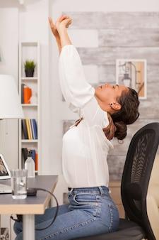 피곤한 여성이 홈 오피스에서 노트북 작업을 하는 동안 등을 쭉 뻗고 있습니다.