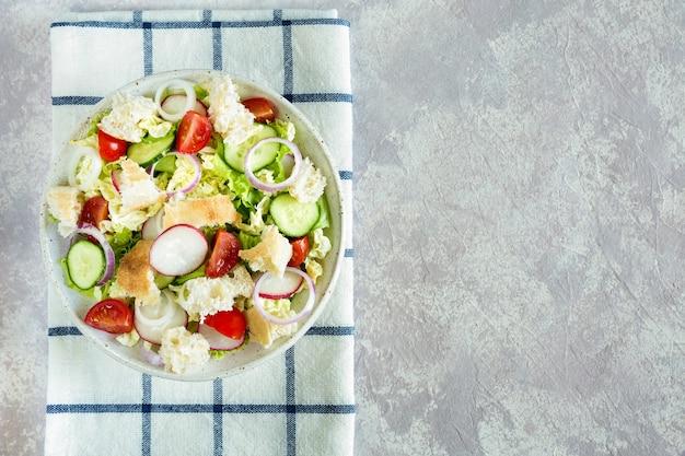 Салат фатуш с лавашем и свежими овощами на тарелке, вид сверху