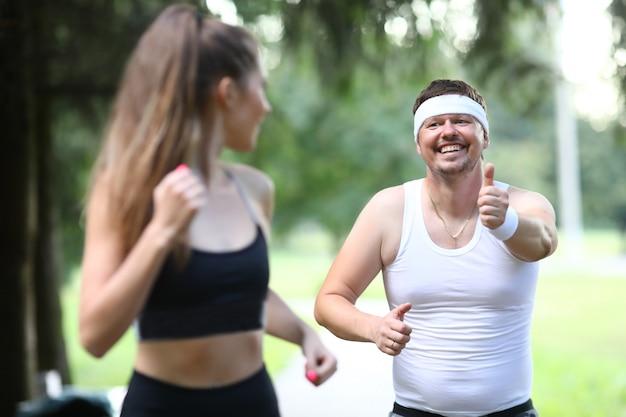 Fatty millennial man running in park with
