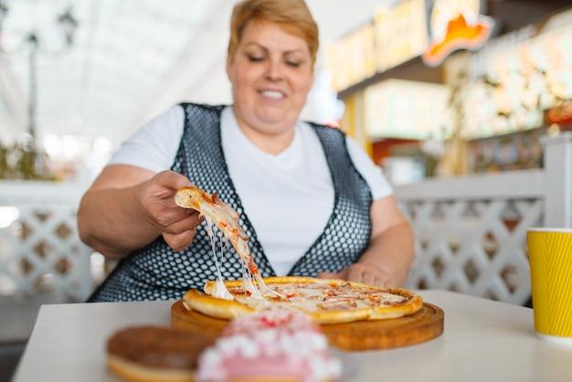 ファストフードレストラン、不健康な食べ物でピザを食べて太った女性。ジャンクディナー、肥満の問題でテーブルで太りすぎの女性人