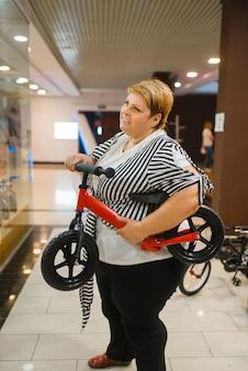 Толстая женщина, держащая маленький велосипед в торговом центре. женщина с избыточным весом с детьми на велосипеде, покупки в супермаркете, проблема ожирения
