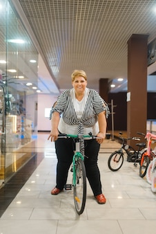 Толстая женщина на велосипеде на витрине в торговом центре. женщина с избыточным весом позирует на велосипеде в супермаркете, проблема ожирения