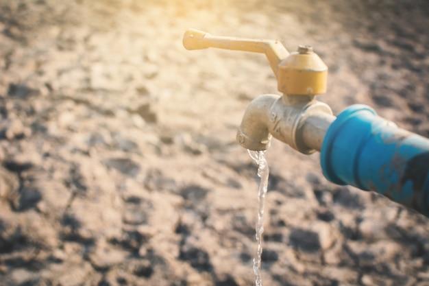 Faucet on cracked dry ground Premium Photo