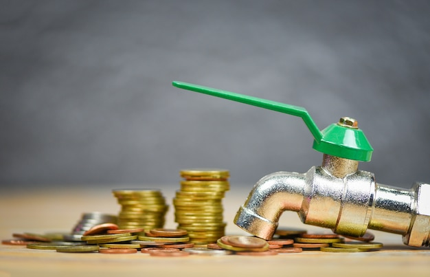 Faucet on money coin wood background / water savings and faucet money fall