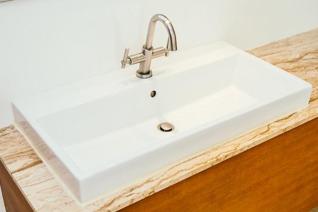 욕실의 수도꼭지 또는 수도꼭지 및 흰색 싱크대 또는 세면기 장식