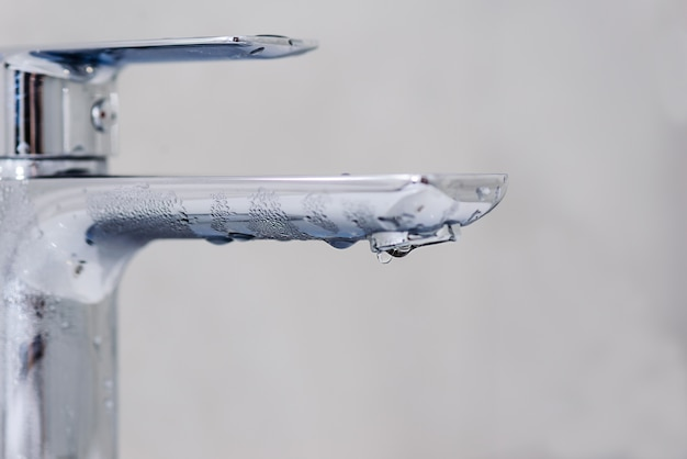 Faucet with a drop of water on a gray background. hot water shutdown concept.