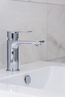 Faucet with a drop of water and a sink on a wall of gray tiles. bathroom interior after renovation. saving water concept.