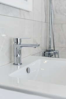 Faucet with a sink in the bathroom with gray tiles. renovation in the bathroom.