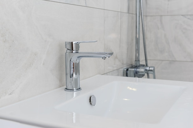 Faucet with a sink in the bathroom with gray tiles.