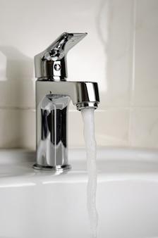 Вода течет из крана или faucet в ванной комнате на белой предпосылке. вертикальный