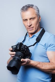 好きな活動は最大の喜びをもたらします。灰色の背景に立っている間カメラを保持しているtシャツで自信を持って年配の男性の肖像画