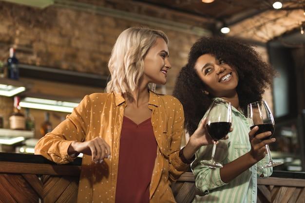好きなアルコール。バーのカウンターの近くに立って、お互いに笑顔でワインを飲むかなり明るい女性