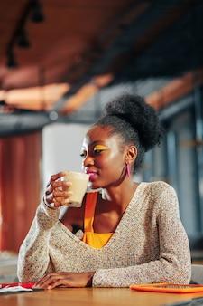 Любимая выпечка. темноволосая кудрявая женщина с ярким макияжем сидит в своей любимой пекарне