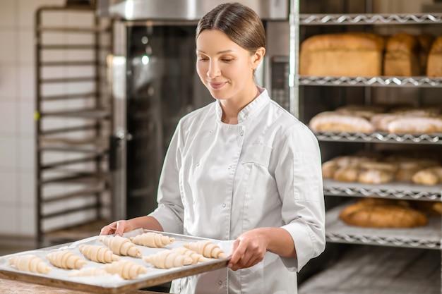 好きなビジネス、パン屋。パン屋を歩いている生のクロワッサンのトレイと制服を着たかなり気配りのある女性の笑顔