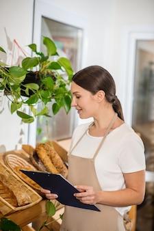 Любимое дело. улыбающаяся длинноволосая женщина в профиль с папкой стоит возле стойки с хлебом и внимательно смотрит с интересом