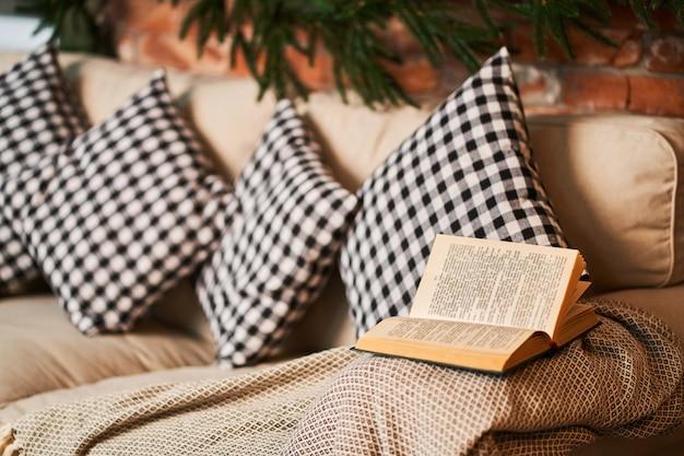 本を読むための市松模様のクッションが付いているお気に入りの居心地の良いソファ