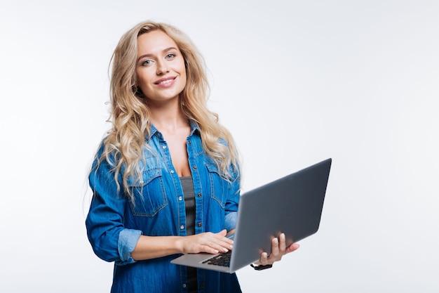 お気に入りのデバイス。灰色の背景に孤立して立っている間ラップトップでポーズをとってデニムシャツの美しい金髪の若い女性