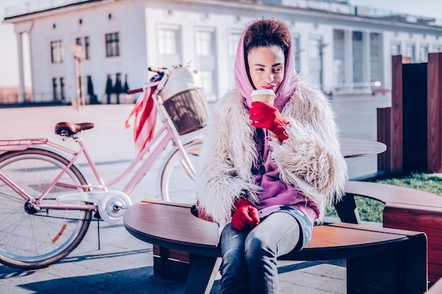 好きな飲み物。散歩の後に休んでいる間彼女の顔に笑顔を保つ陽気な浅黒い肌の女の子