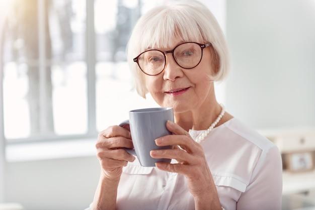 好きな飲み物。魅力的な高齢女性のポーズと青いカップからコーヒーを飲みながら笑顔のクローズアップ