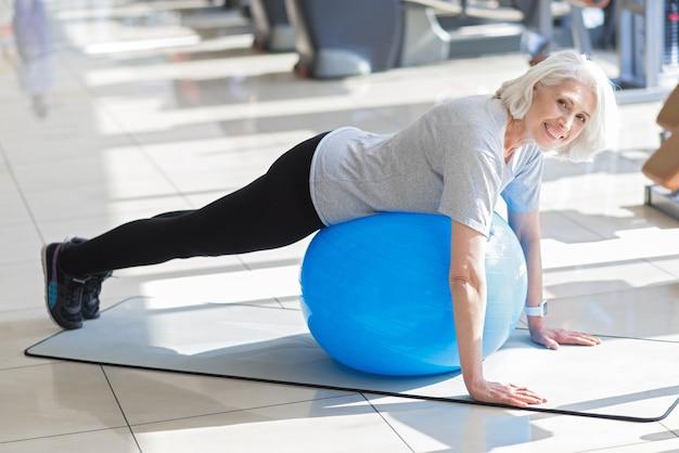 Любимое упражнение. вдохновленная красивая старшая женщина с мячом в форме и улыбается во время тренировки в тренажерном зале.
