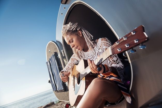 好きなメロディー。トレーラーハウスに座ってお気に入りのメロディーを演奏するアフリカ系アメリカ人のクリエイティブミュージシャン