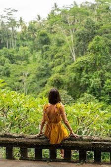 お気に入りの場所。石のサポートに座って島での生活を夢見ている陽気な女性