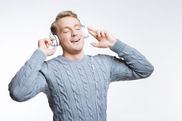 가장 좋아하는 노래. 흰색 헤드폰으로 음악을 듣고 영감을 얻은 회색 스웨터에 매력적인 국방과 젊은 남자