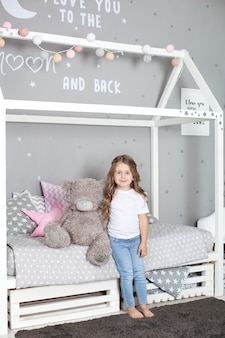 Favorite toy. girl child sit on bed hug teddy bear in her bedroom. kid prepare to go to bed. pleasant time in cozy bedroom.  a child plays in his children's room with a toy. children's room decor