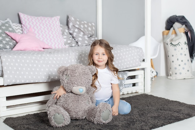 Favorite toy. girl child sit on bed hug teddy bear in her bedroom. kid prepare to go to bed. pleasant time in cozy bedroom. girl kid long hair cute pajamas relax and play plush teddy bear toy.
