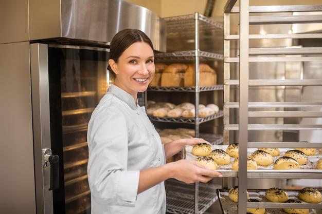 좋아하는 작품. 빵집 선반에 빵과 베이킹 시트를 넣어 흰색 재킷에 친절 꽤 웃는 여자