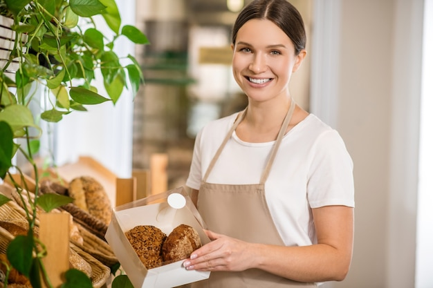 좋아하는 작품. 가게에서 좋은 분위기의 상자에 빵 빵과 앞치마에 행복 귀여운 젊은 성인 여자 프리미엄 사진