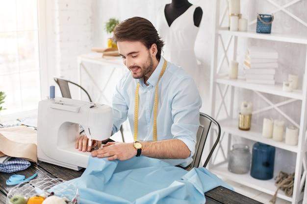 좋아하는 활동. 웃고 재봉틀에서 일하는 무성한 검은 머리 재단사