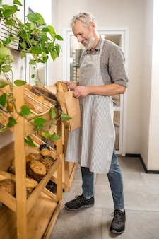 Любимое дело. взрослый седой улыбающийся мужчина в фартуке стоит возле стойки пекарни, кладет хлеб в бумажный пакет